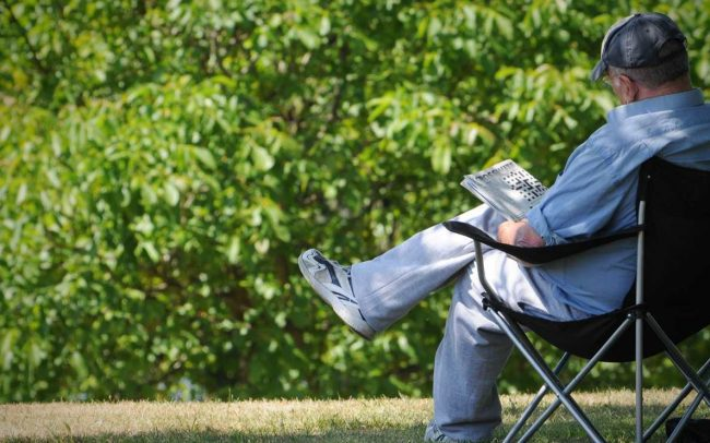man relaxing, reading the newspaper in cyfartha park