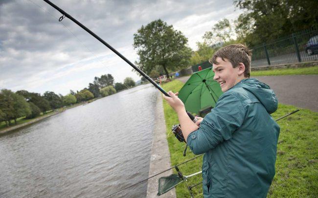 teenagers lerning to fish in cyfartha park