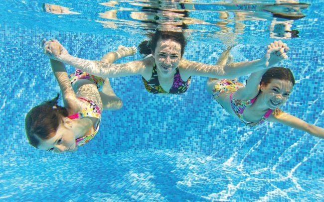 family swimming in swimming pool